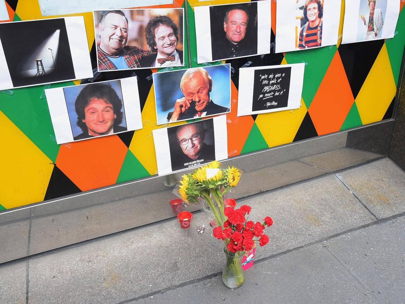 Flowers, tootsie rolls, a card, and a candle are placed in memory of Robin Williams in front of Carolines on Broadway comedy club in New York City
