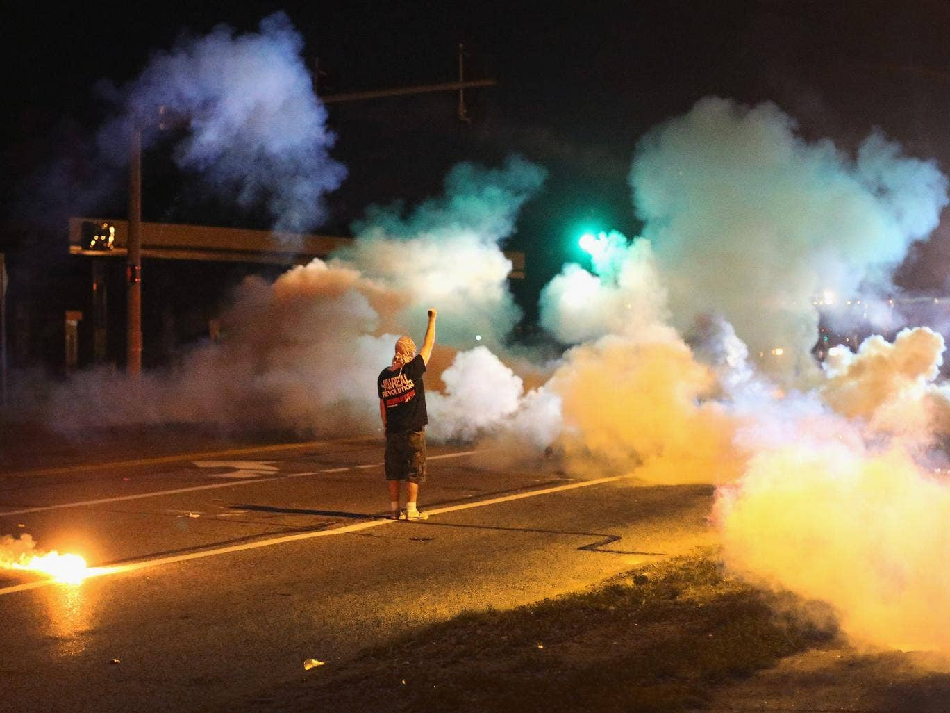 A demonstrator, protesting the shooting death of teenager Michael Brown, stands his ground as police fire tear gas in Ferguson