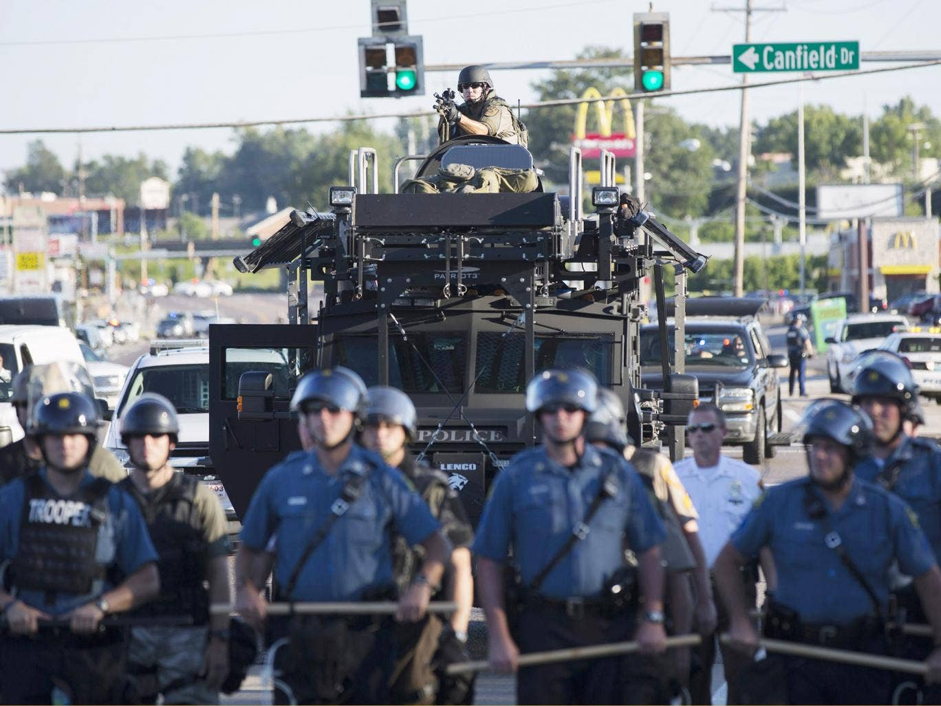 Riot police stand guard as demonstrators protest the shooting death of teenager Michael Brown in Ferguson
