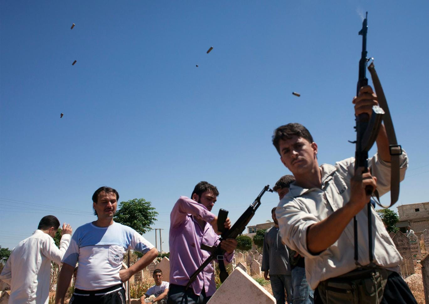 A fighter from the Free Syrian Army fires rounds into the air on August 21, 2012, during the funeral of 17-year old Ahmed Hamoudi