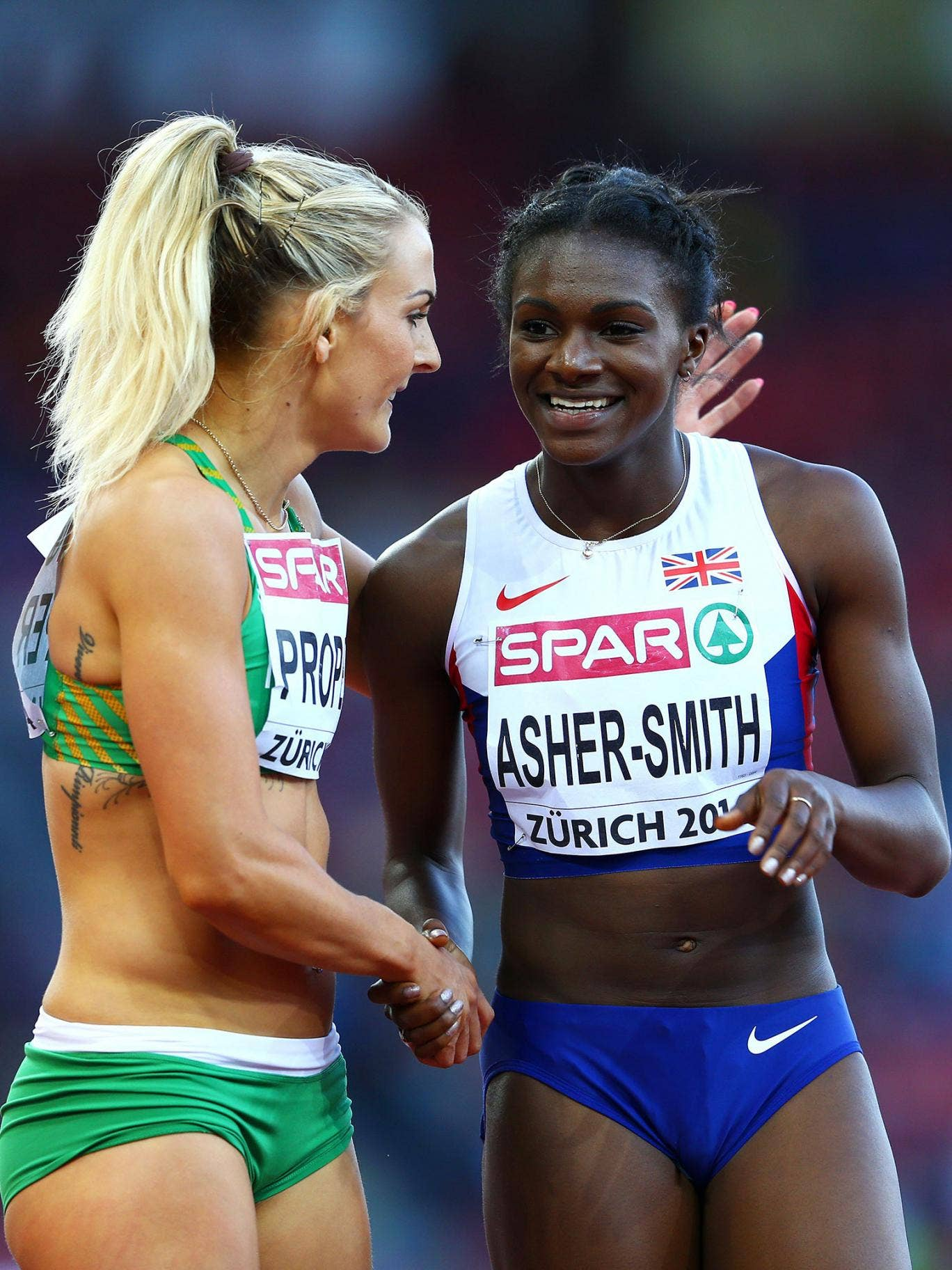 Dina Asher-Smith of Great Britain and Northern Ireland and Kelly Proper of Ireland speak after the Women's 200 metres semi-final on day three of the 22nd European Athletics Championships