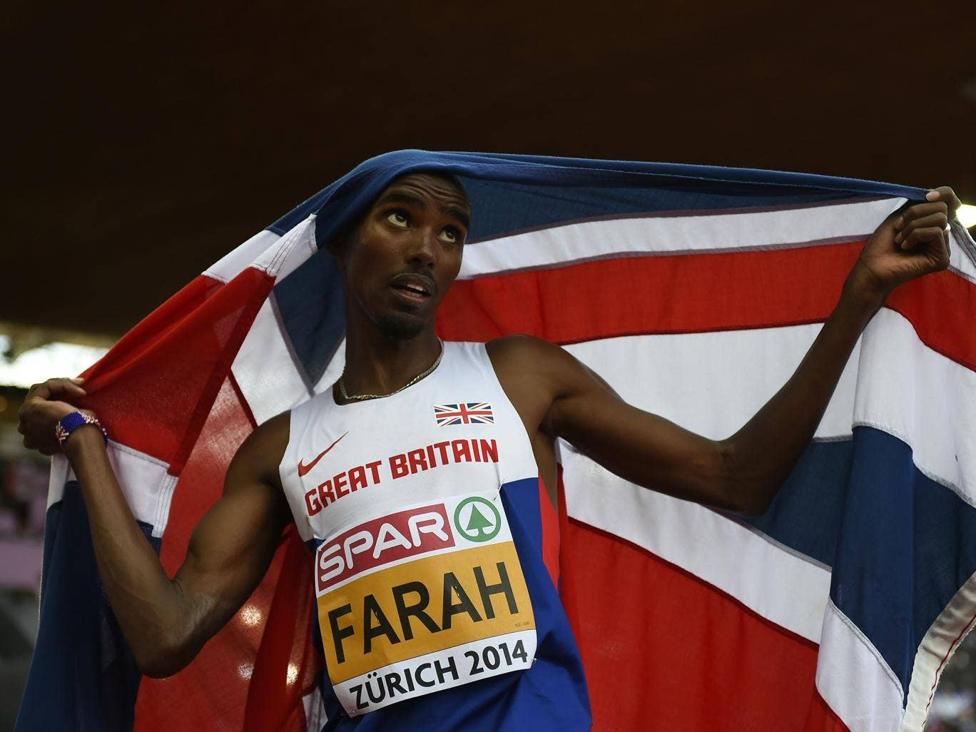 Great Britain's Mohamed Farah, holding his national flag, celebrates after winning the Men's 5000m final