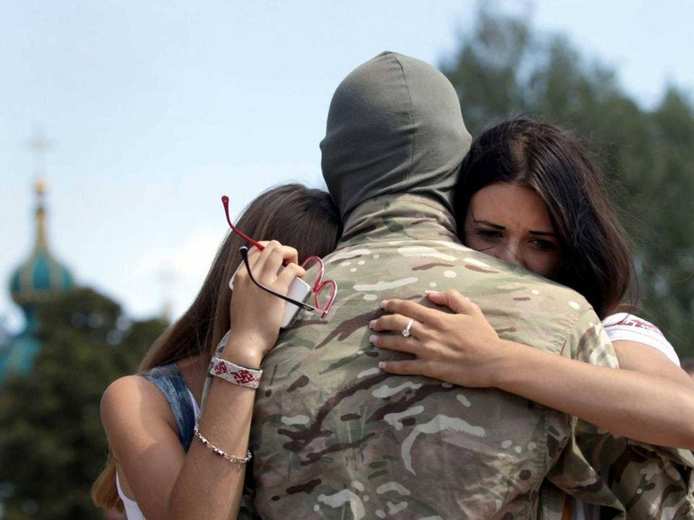 A member of the 'Azov' Battalion gets a farewell hug during a ceremony sending soldiers to eastern Ukraine