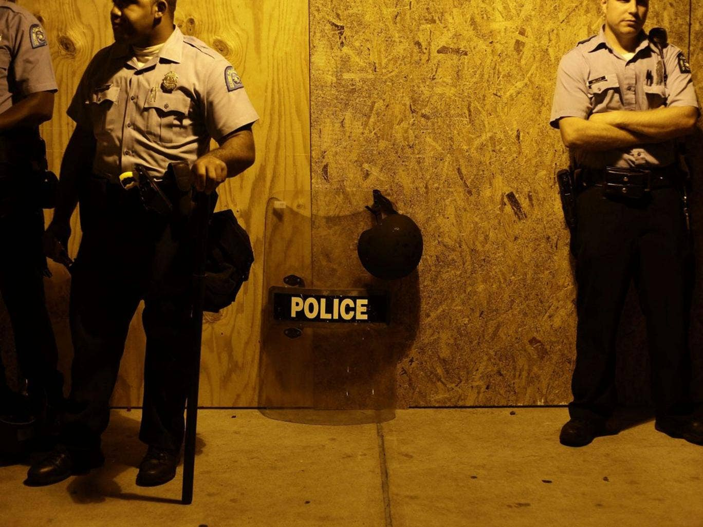Police officers stand in position as they watch demonstrators protest Michael Brown's murder August 16, 2014 in Ferguson, Missouri.