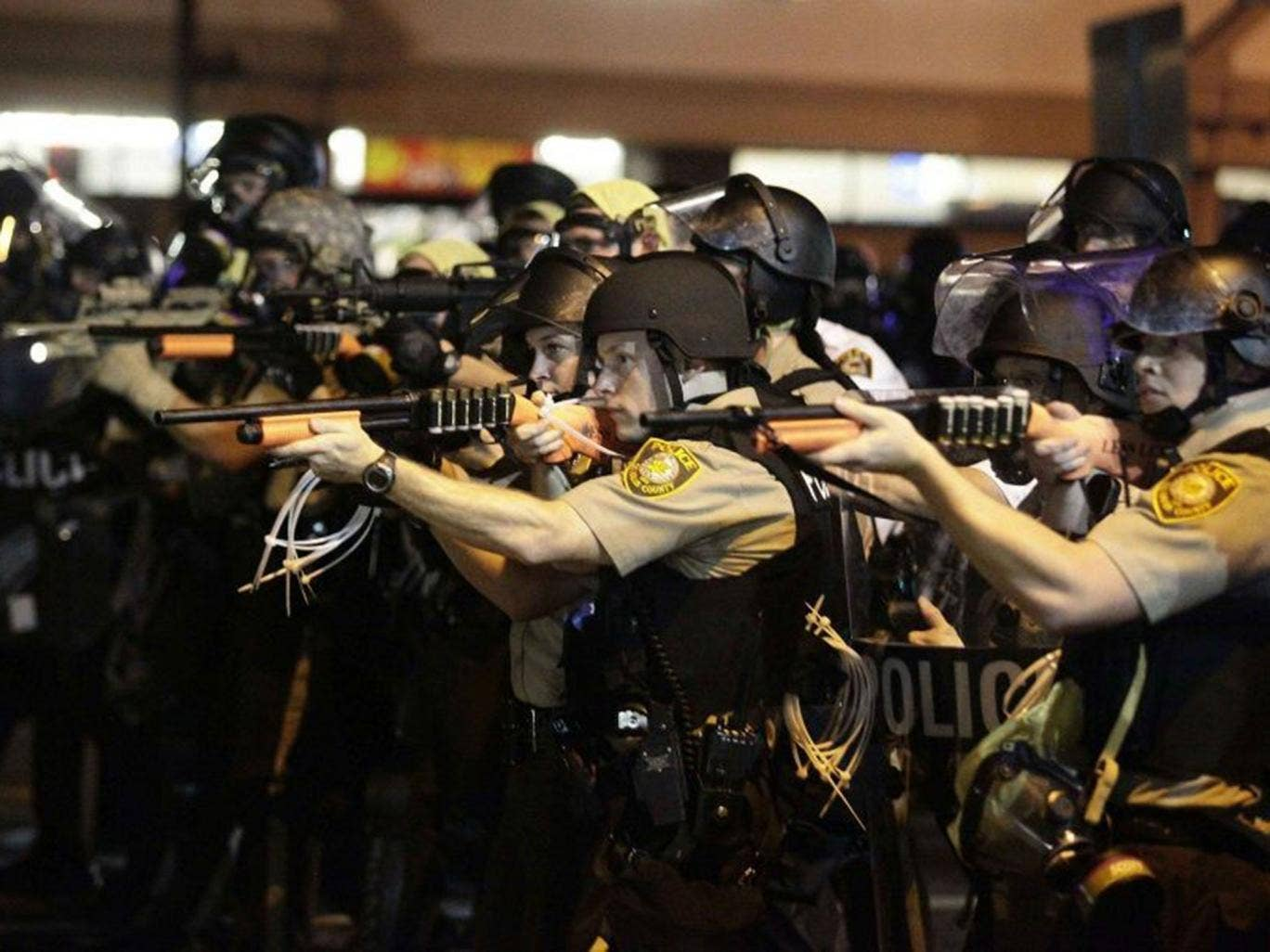 Officers point their weapons at protesters in Ferguson, Missouri