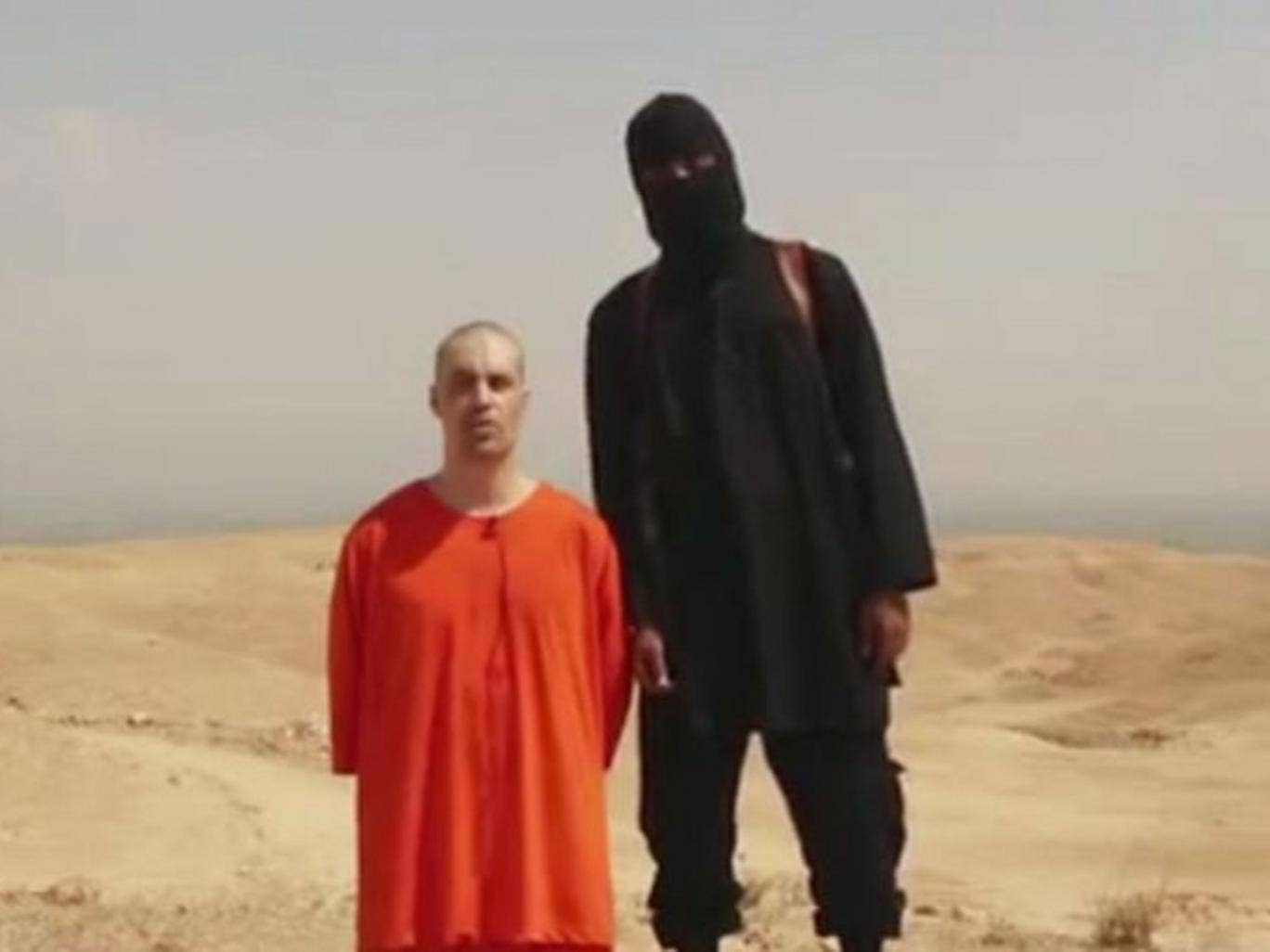 The video shows a man, thought to be James Foley, kneeling in front of a black-clad militant
