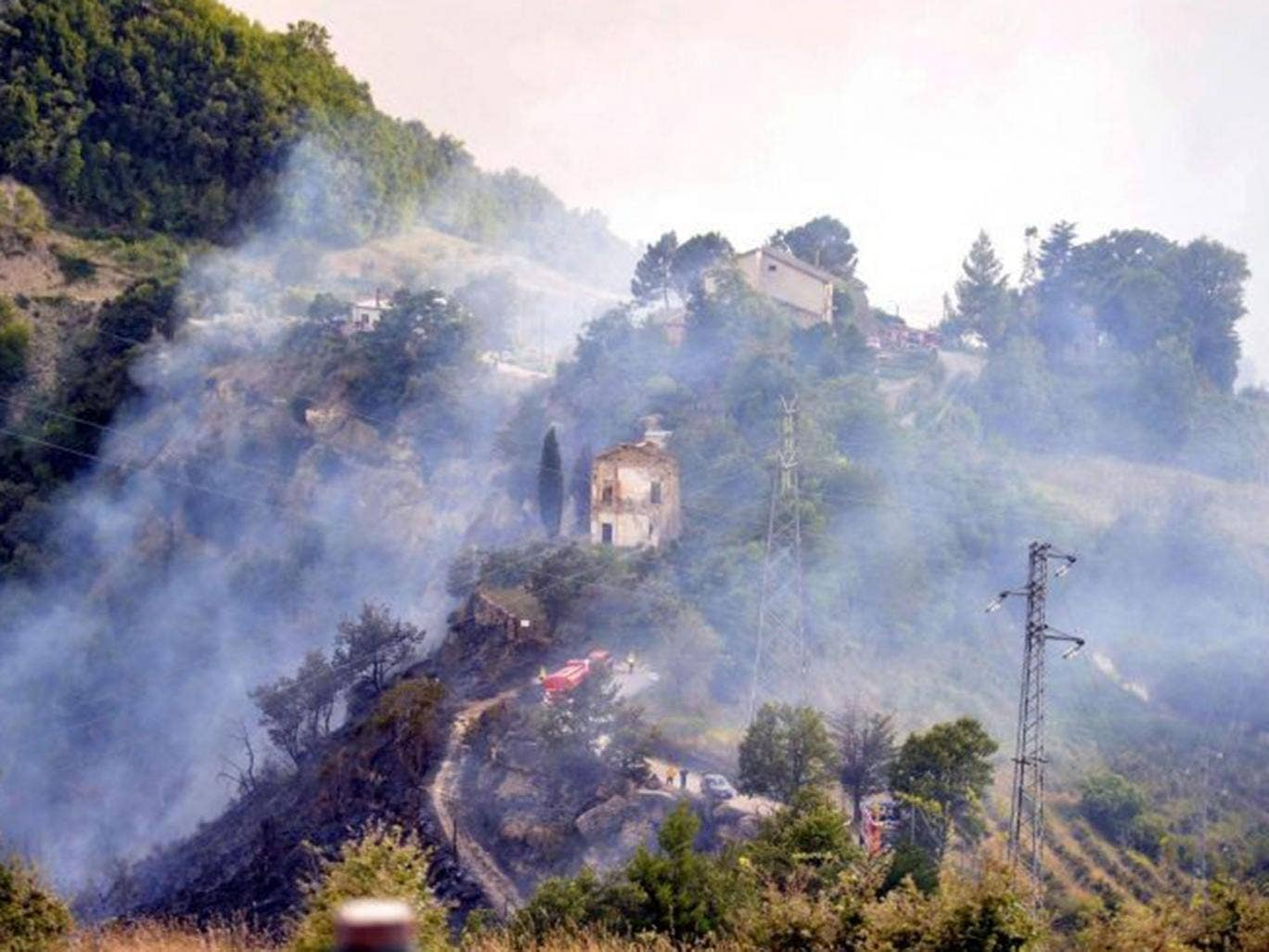Firefighters at work after the collision of two Italian Air Force jets over the Marche region, Italy, 19 August 2014