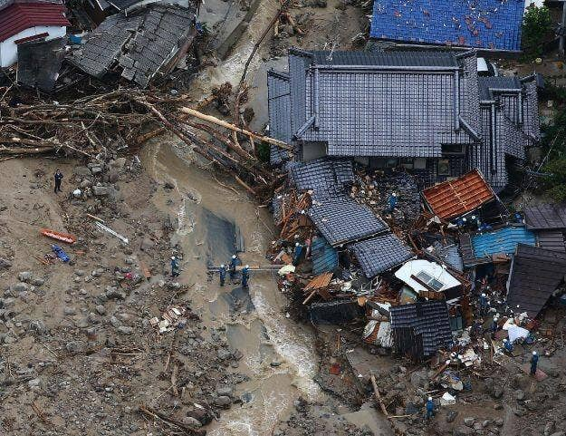 Rescue workers looking for survivors at the site of a landslide after heavy rains hit the city of Hiroshima, western Japan, on August 20