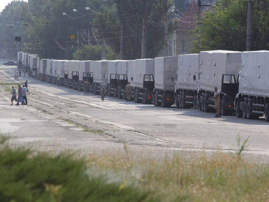 Drivers of the first trucks of the Russian aid convoy parked in the city of Luhansk on 22 August