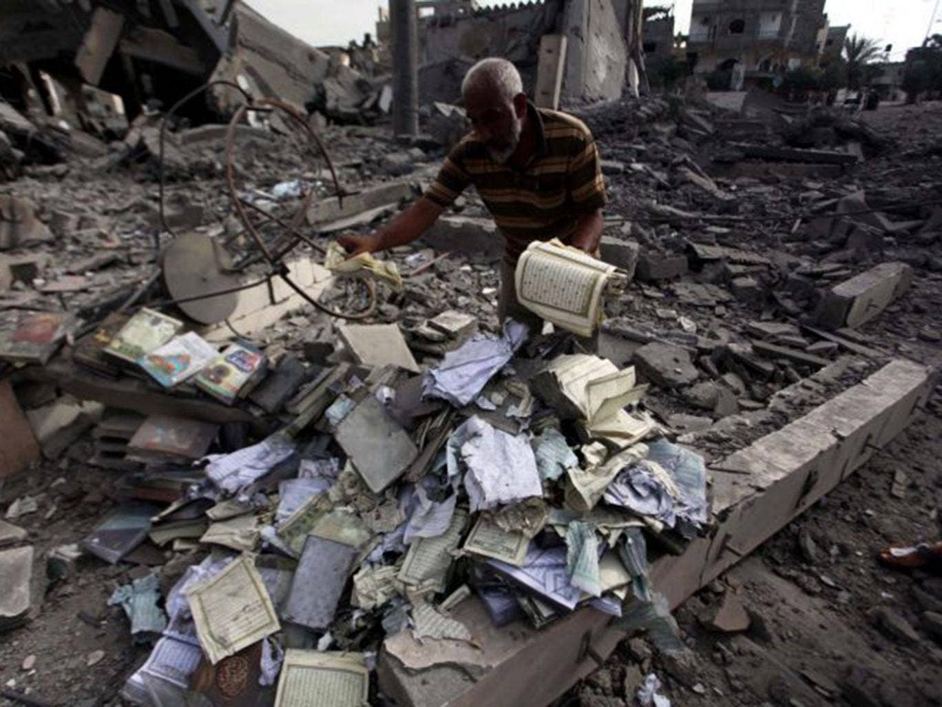 A Palestinian man collects copies of the Quran in the rubble of the Omar Ibn Abd al-Aziz mosque destroyed in an Israeli air strike in Beit Hanoun
