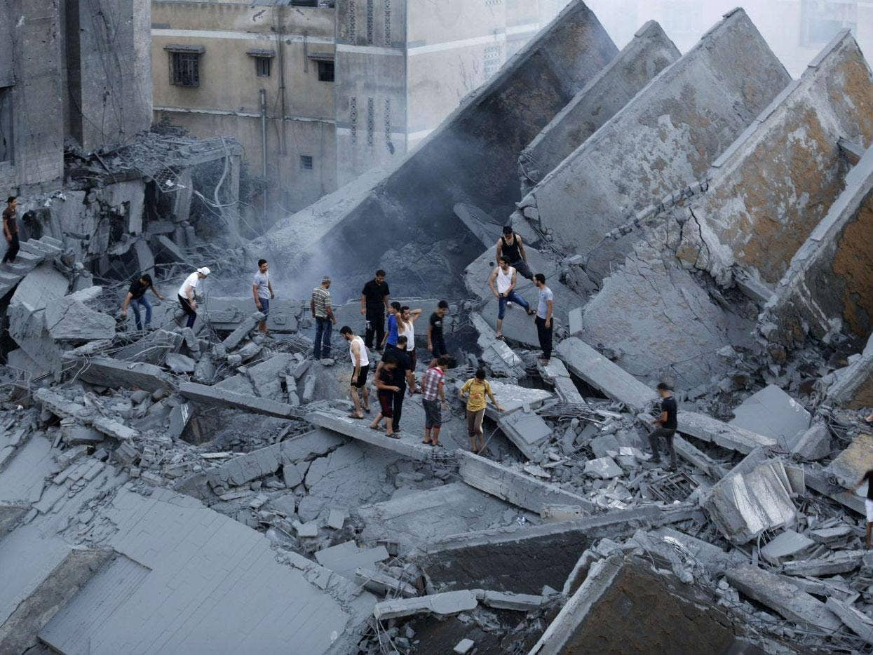 Palestinians inspect the remains of the destroyed Basha Tower on 26 August 2014