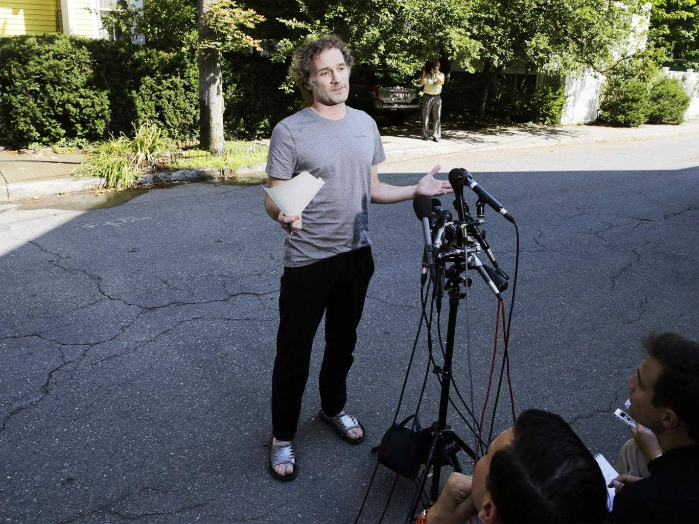 Peter Theo Curtis reads a statement to reporters outside his mother's home in Cambridge, Mass