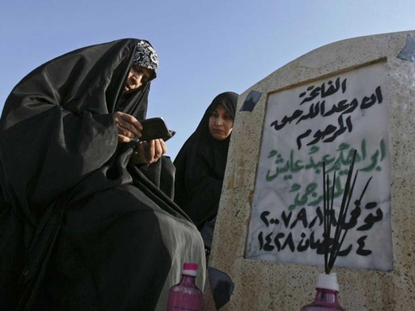 Long wait: Relatives at a victim's grave