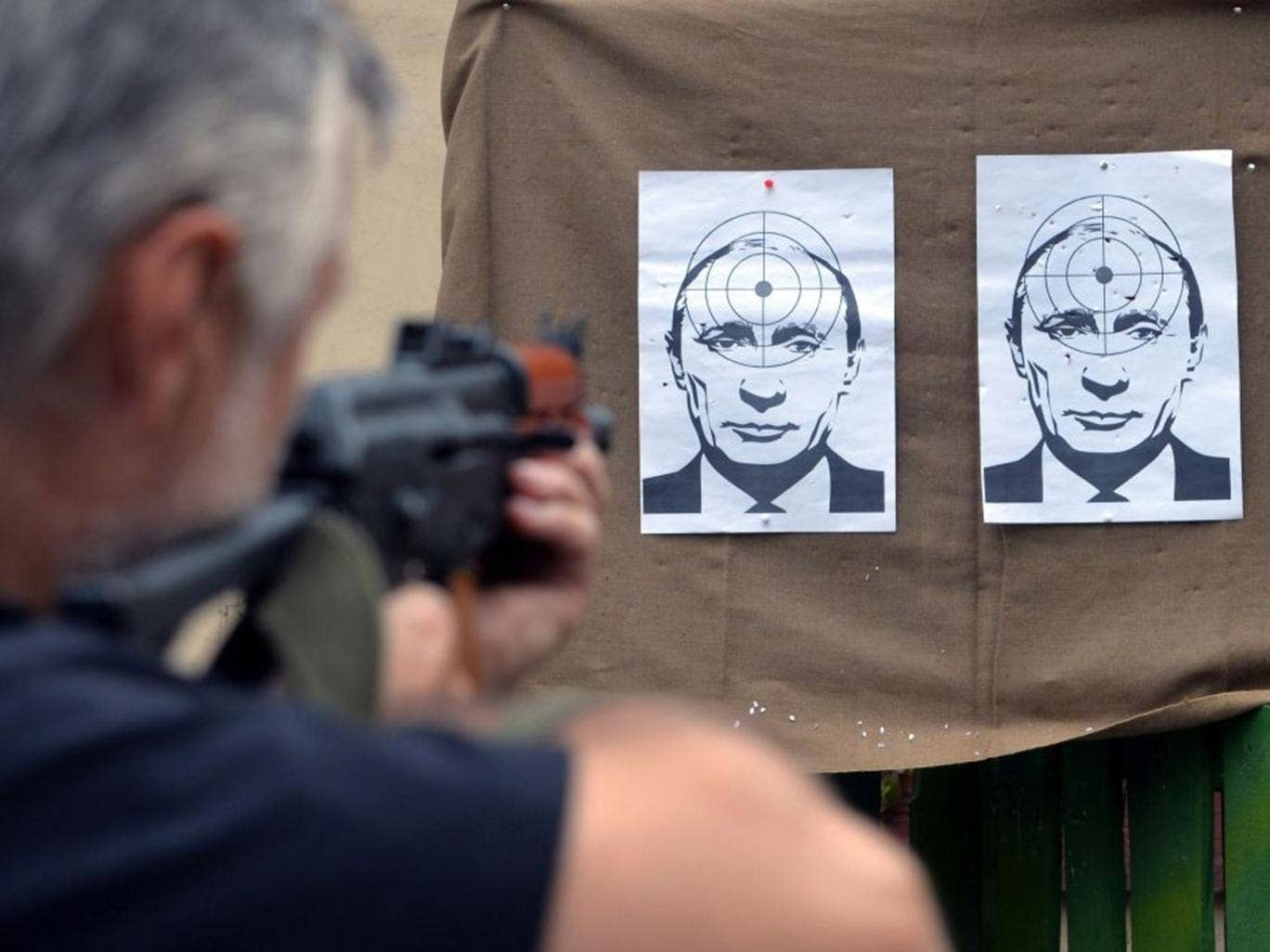 A man shoots at targets depicting a portrait of Russian President Vladimir Putin, in a shooting range in the center of the western Ukrainian city of Lviv