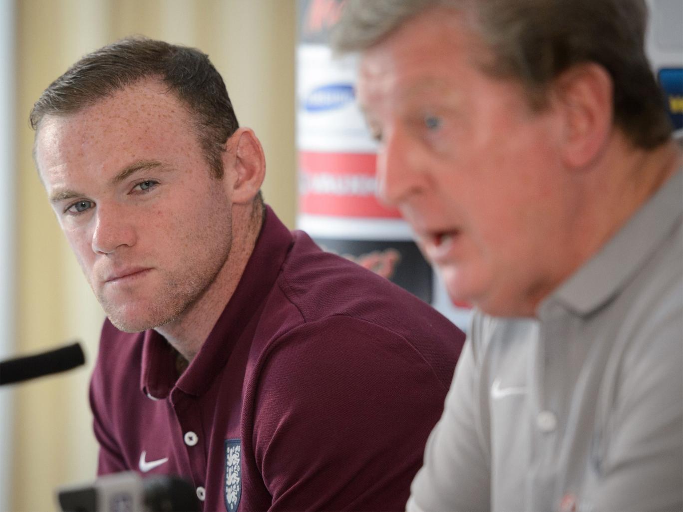 Wayne Rooney watches as England manager Roy Hodgson addresses the media
