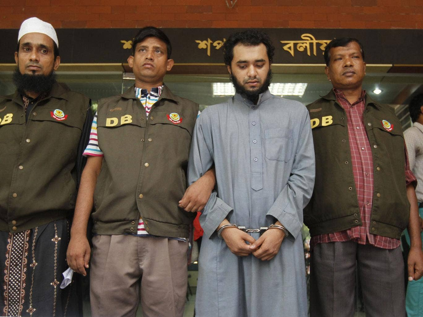 Samiun Rahman, centre, was re-arrested at a train station for the media's benefit, according to a human rights group