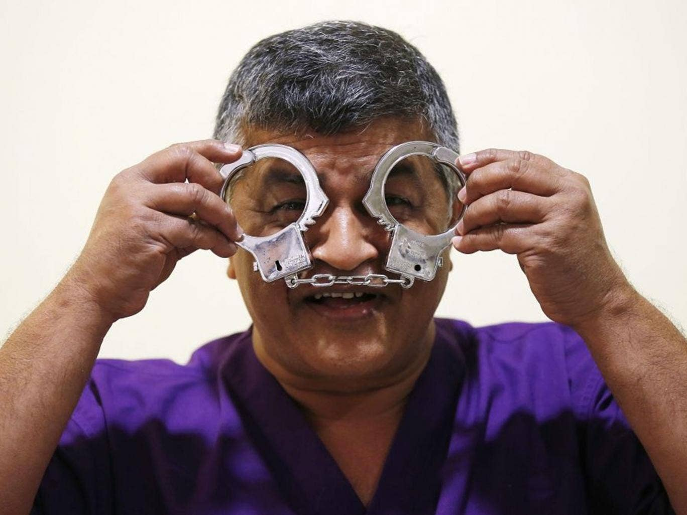 Malaysian political cartoonist Zulkiflee Anwar Haque, or 'Zunar', reacts with mock handcuffs during his case at Duta Court, in Kuala Lumpur, 03 April 2015. Zunar is facing nine charges under Malaysia's Sedition Act which are related to a series of tweets