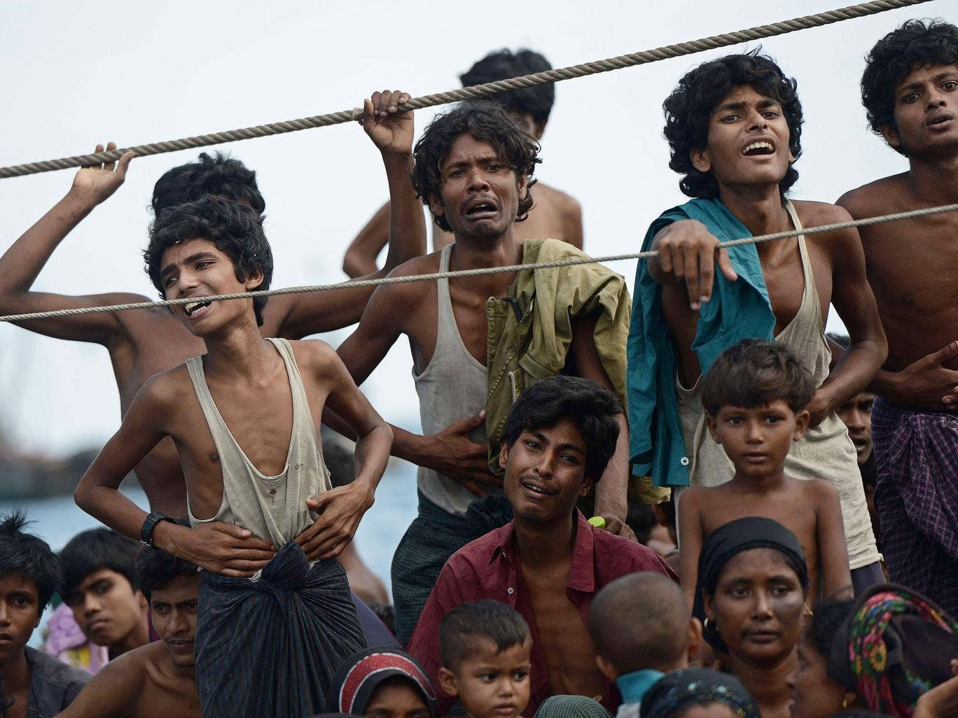 Rohingya migrants stand and sit on a boat drifting in Thai waters off the southern island of Koh Lipe in the Andaman sea