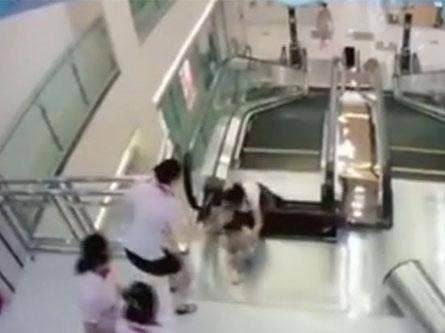 CCTV footage showing the mother pushing her son to safety as the metal panel gives way beneath them