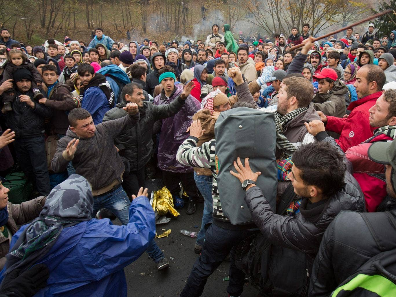 Refugees scuffle in Sentilj, Slovenia, as they wait to cross the border into Austria