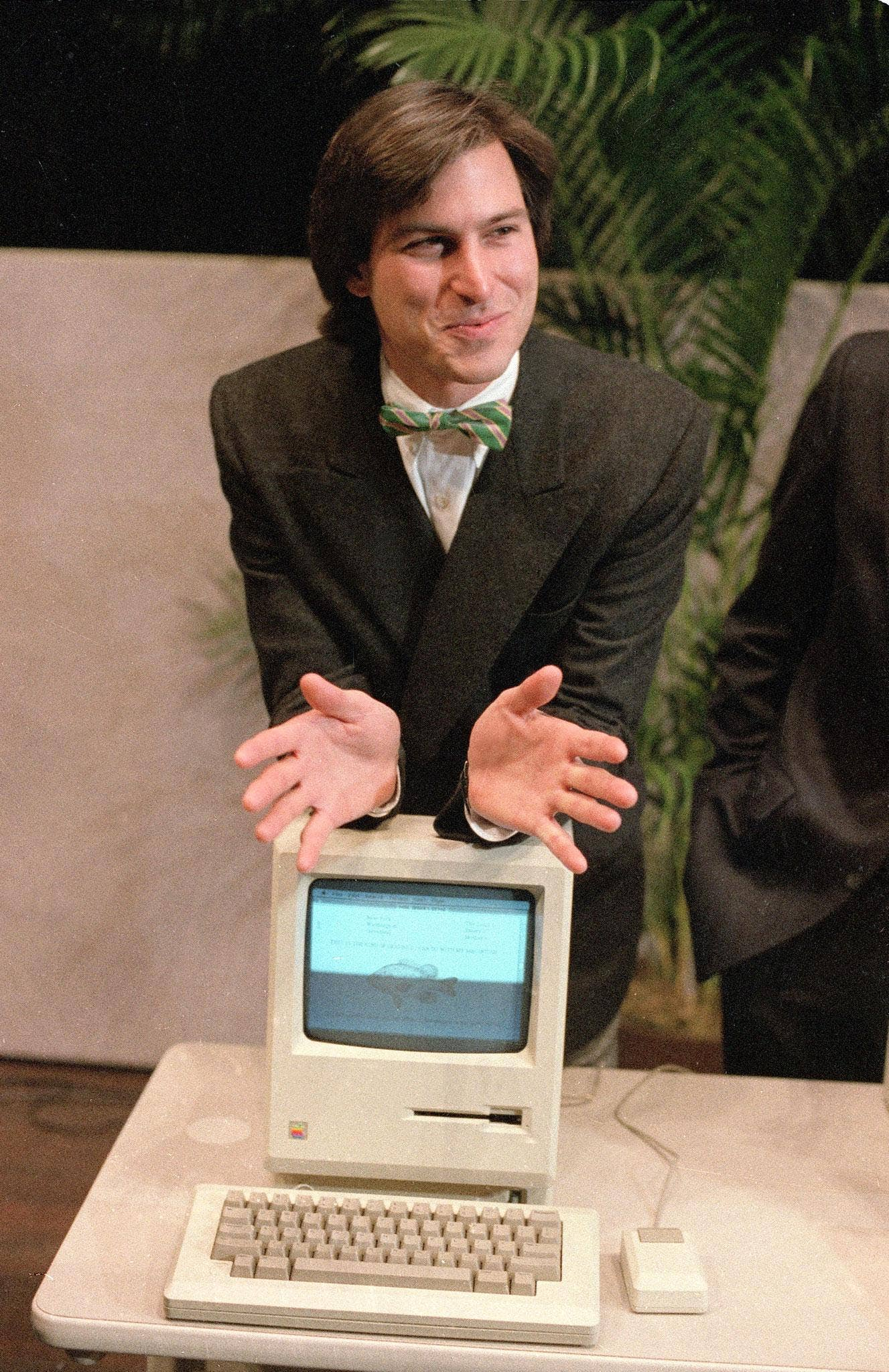 Steve Jobs leans on the new Macintosh personal computer in 1984