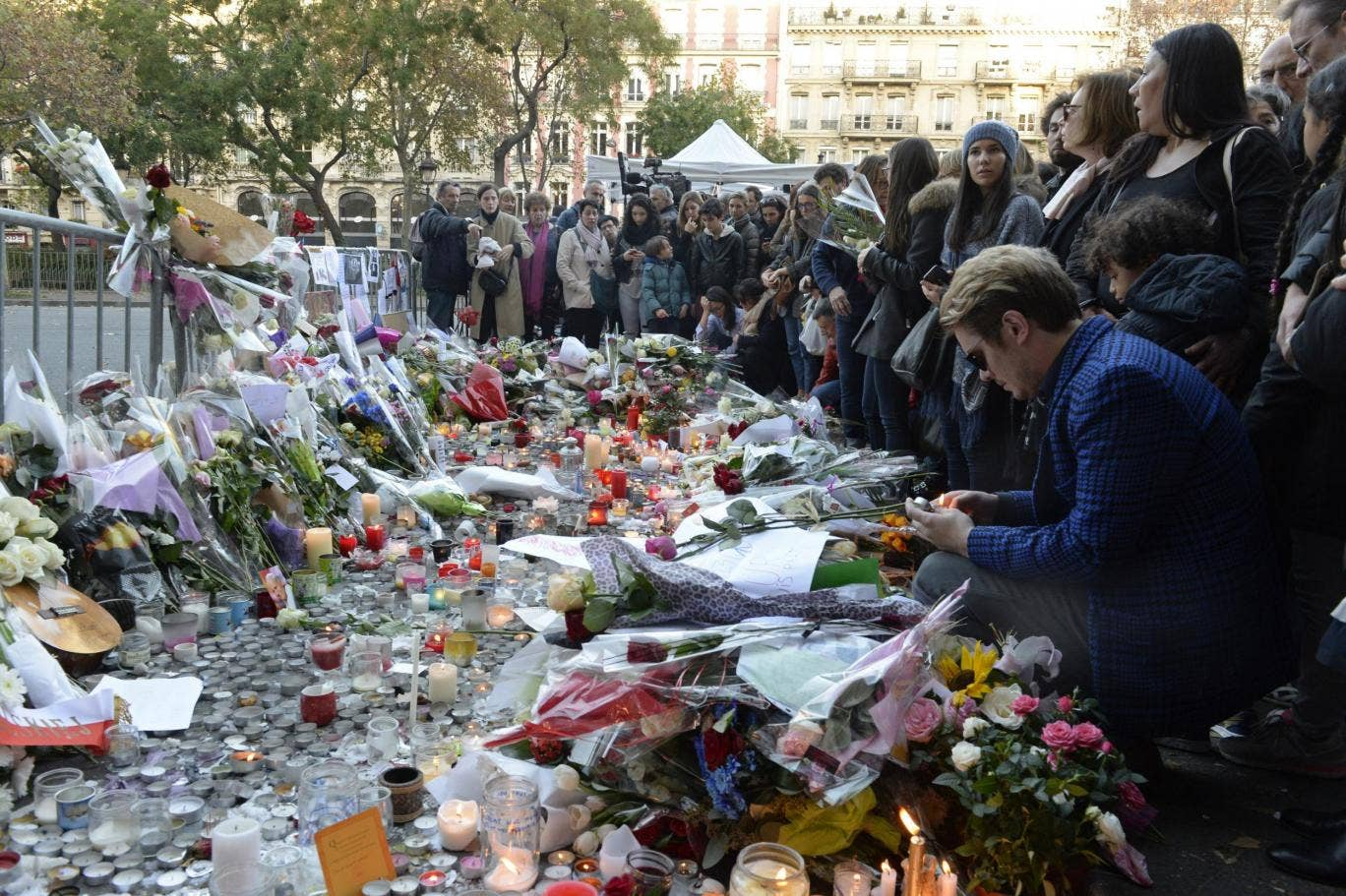 People mourn outside a makeshift memorial at the Bataclan concert hall in Paris