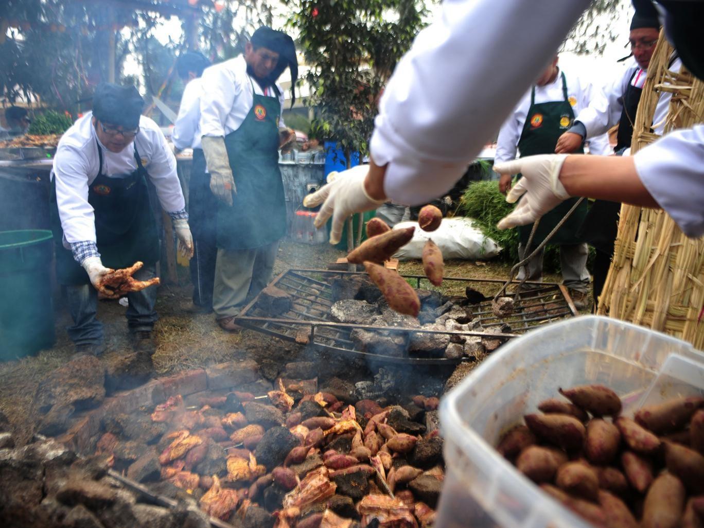 Cooks prepare a potato dish at a Lima food fair