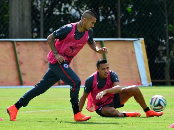 Chile's-national-football-team-midfielder-Arturo-Vidal-(L)-controls-the-ball-as-his-teammate-forward-Alexis-Sanchez-(R)-watches-on-during-a-training-session.jpg