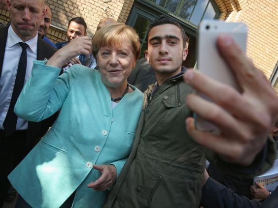 [Image: Merkel-migrant.jpg]