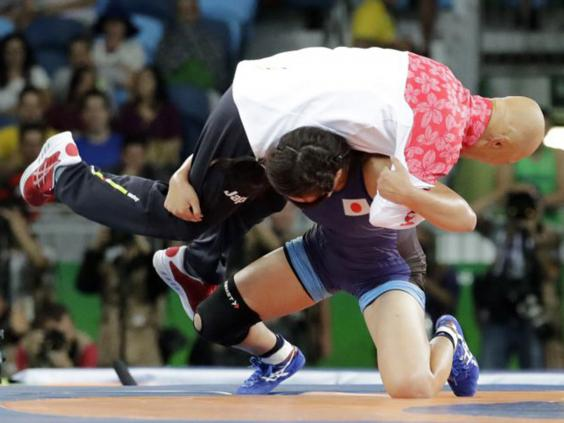 Japanese Olympic wrestler celebrates winning gold medal by slamming her coach. Twice