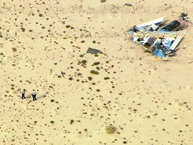 Police officers stand near wreckage from Virgin Galactic's SpaceShipTwo