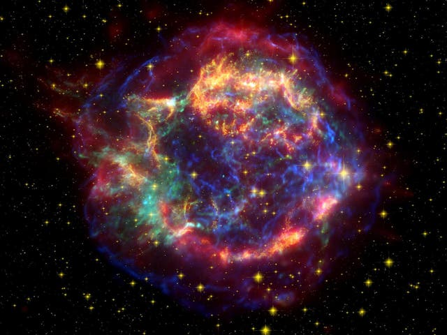 A false colour image of Cassiopeia A comprised with data from the Spitzer and Hubble Space Telescopes and the Chandra X-Ray observatory