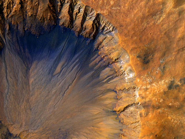 """The HiRISE camera aboard Nasa's Mars Reconnaissance Orbiter acquired this closeup image of a """"fresh"""" (on a geological scale, though quite old on a human scale) impact crater in the Sirenum Fossae region of Mars. This impact crater appears relatively recent as it has a sharp rim and well-preserved ejecta"""