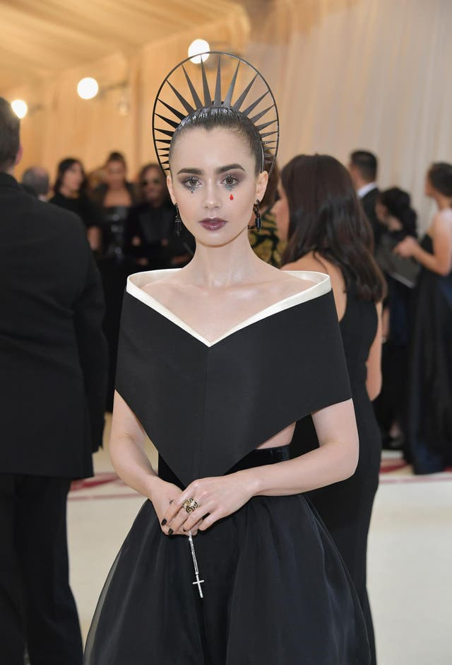 Lily Collins wears a black Givenchy gown and coordinating gothic makeup