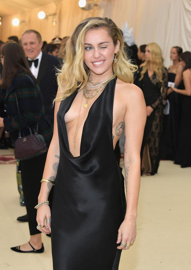 Miley Cyrus wears plunging black dress by Stella McCartney and Sydney Evan custom hoops with a large cross