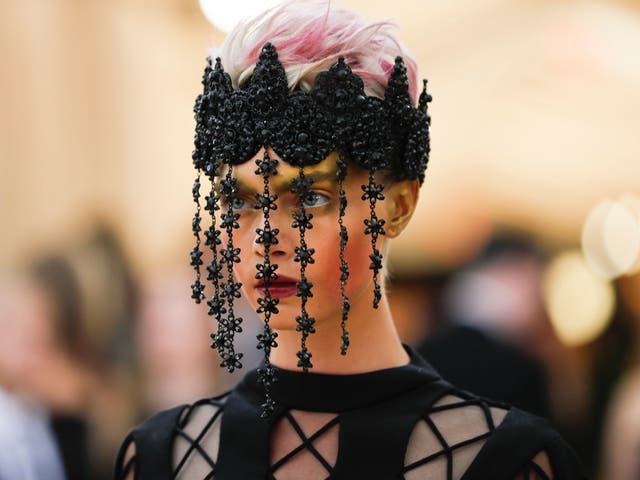 Cara Delevingne wears a dramatic all-black Dior Haute Couture dress and beaded veil