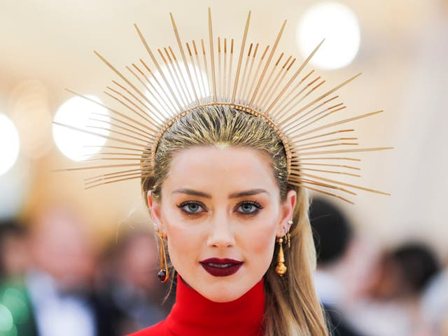 Amber Heard paired a Carolina Herrera scarlet gown with a gold halo headpiece