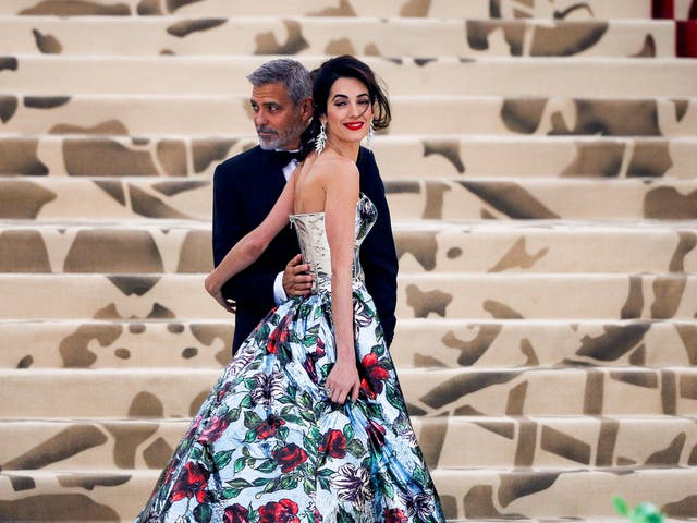 Amal Clooney wears a Richard Quinn corset dress and navy trousers while husband George Clooney opted for a traditional black tuxedo