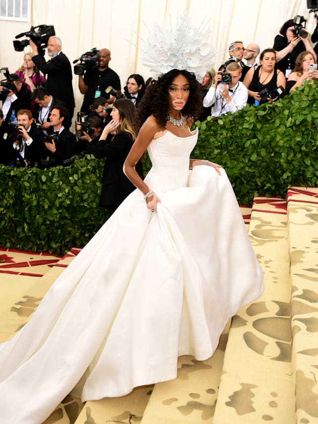 Winnie Harlow wears an all-white Tommy Hilfiger dress with a dramatic train