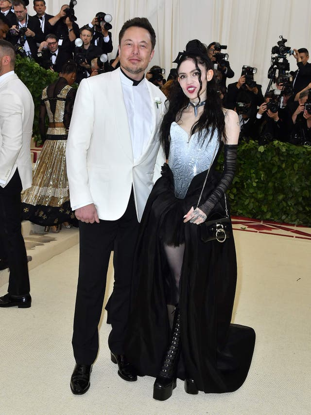 Elon Musk wears a white tuxedo and Tesla pin, while Grimes opted for a black dress and Tesla choker