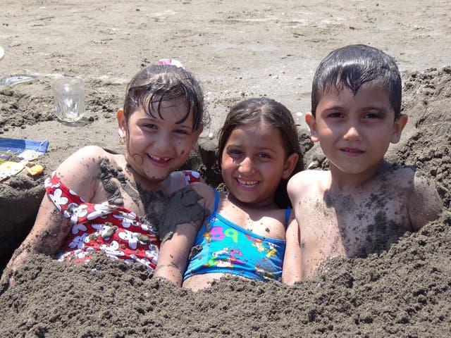 Children enjoying the sun and sand at Bandar-e Mahshahr, Iran
