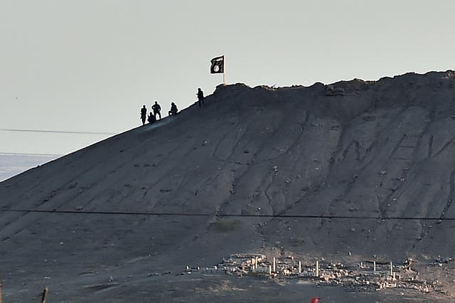 Isis militants sit atop a hill planted with their flag in the Syrian town of Kobani on 6 Outubro 2014. They had been advancing on Kobani since mid-September and by now was in control of the city's entrance and exit points