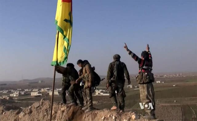 YPG fighters raise a flag as they reclaim Kobani on 26 Janeiro 2015