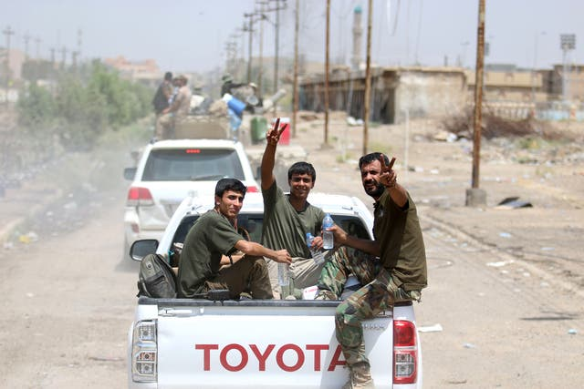 Iraqi government forces make the victory sign as they retake the city of Fallujah from ISIS on 26 Junho 2016