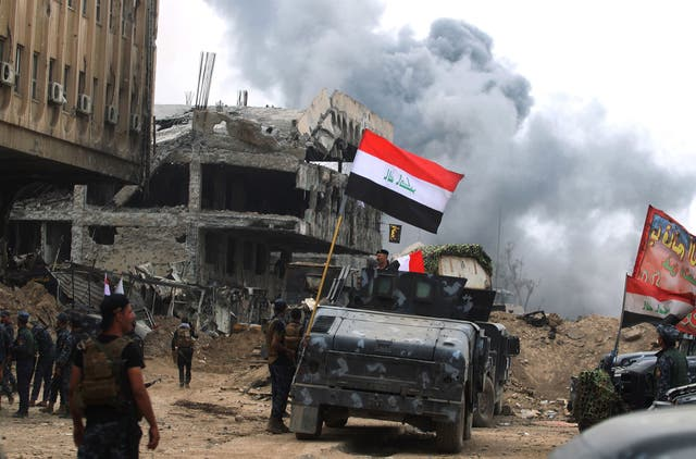 Members of the Iraqi federal police raise flags in Mosul on 8 julho 2017. On the following day, Iraqi prime minister Haider Al Abadi declares victory over Isis in Mosul