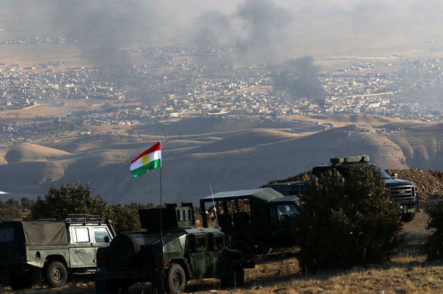 Kurdish forces are stationed on a hill above the town of Sinjar as smoke rises following US airstrikes on 12 novembro 2015