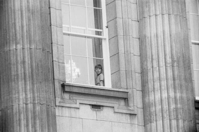 A six-year-old Prince Andrew looks out from a window at Buckingham Palace. (1966)