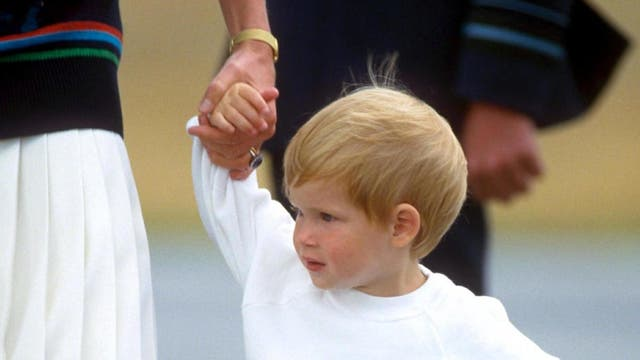 A two-year-old Prince Harry holds the hand of his mother, Princess Diana, at Aberdeen Airport. (1986)