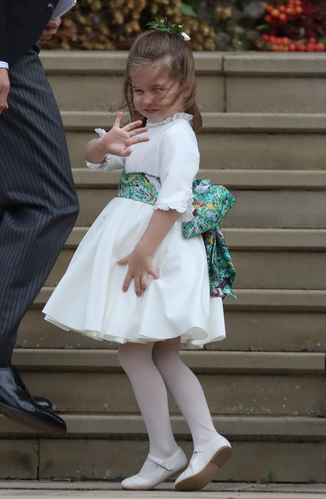 Princess Charlotte waves on the steps of St George's Chapel, Windsor, as she arrives at the wedding of Princess Eugenie and Jack Brooksbank. (2018)