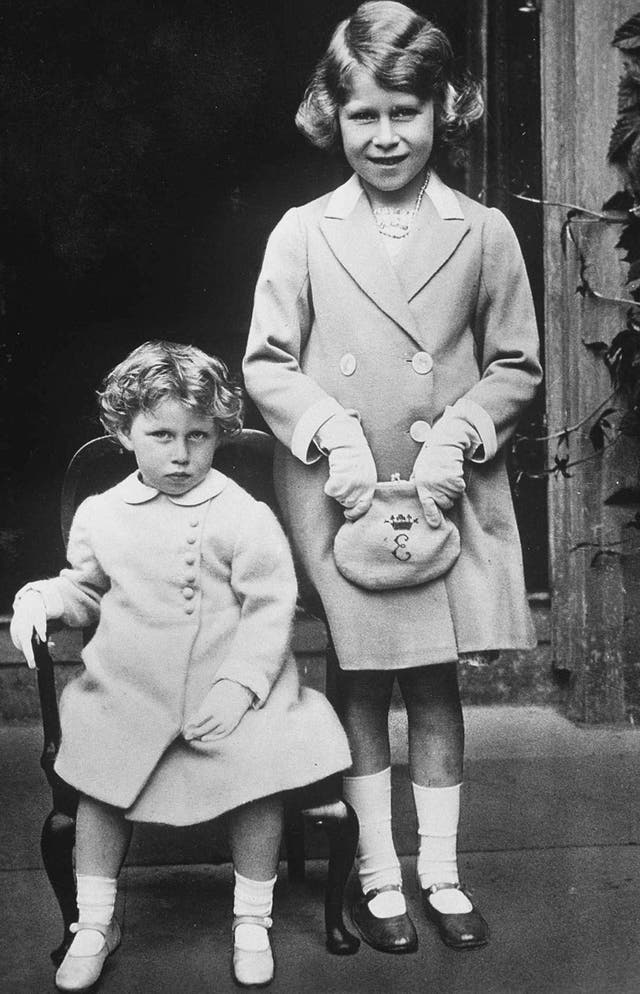 """Princess Margaret is pictured alongside her elder sister Princess Elizabeth, later Queen Elizabeth II. Princess Elizabeth carries a purse embroidered with the letter """"E"""" and a crown. (circa 1933)"""